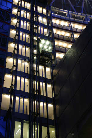 elevation: Corporate night elevation with a glass lift and inner white lighting