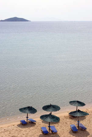 horizont: Beach chairs and umbrellas on a dream beach - small island on the horizont. Stock Photo