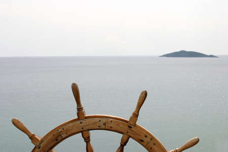water wheel: Old ships steering wheel on great ocean background with a small island ahead.