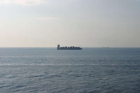 horizont: Fully loaded container carrier ship on the horizont.