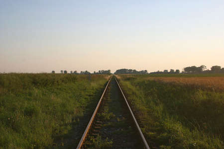 railtrack: Single railtrack going straight ahead in a clear glass field at sunset. Stock Photo
