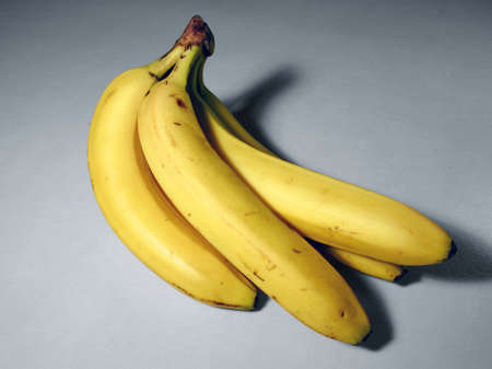garish: A bunch of bananas on a white flat surface.