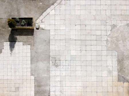patched: Upper view of a square filled with pavement tiles and patched with concrete
