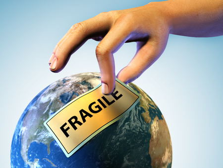 breakable: Male hand applying a fragile label on planet Earth. Digital illustration. Stock Photo
