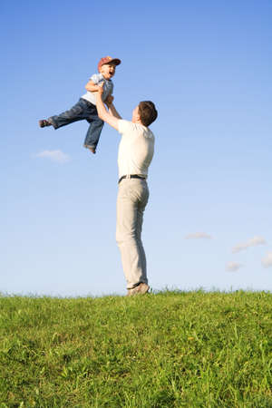 revolve: Young boy play with father. Green grass. Blue sky. 5