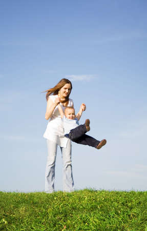 revolve: Young boy play with mother. Blue sky. Green grass. 5 Stock Photo