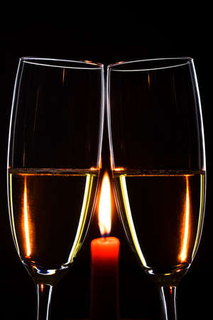 burning love: Romantic evening. Glasses. Champagne. Candle. Black background. Vertical Stock Photo