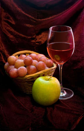 Red vine, grapes and apple. Red background photo