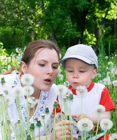 Boy with mother on the meadow. Flowers. 7 photo