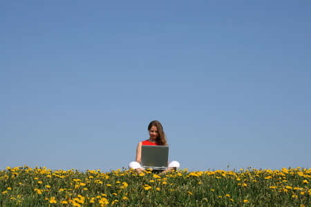Casual woman working with notebook in a flowering dandelion field. Stock Photo - 963892