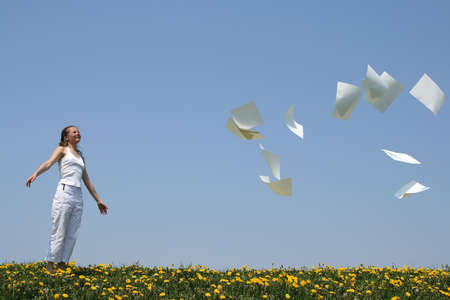 liberate: Smiling girl frees herself from paperwork and looks at blank paper sheets (with copy space) going away with the wind. Stock Photo