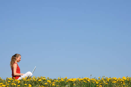 Nice girl working with laptop outdoors, in a flowering field. Stock Photo - 1005226
