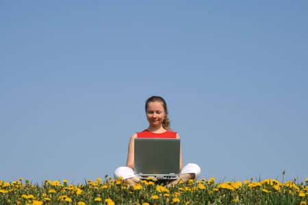 Casual young woman working with laptop outdoors, in a flowering field. photo