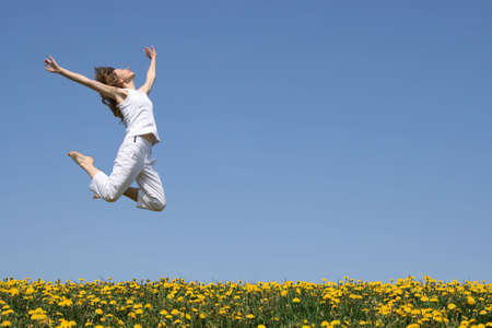 Young woman in a beautiful happy jump in flowering field. photo