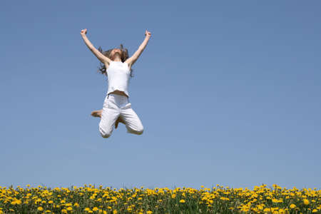 Smiling girl in a happy jump, looking up, in a flowering field. photo