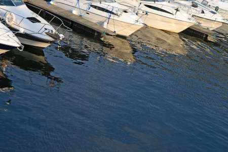 motorboats: Motorboats in a harbor reflecting in water.