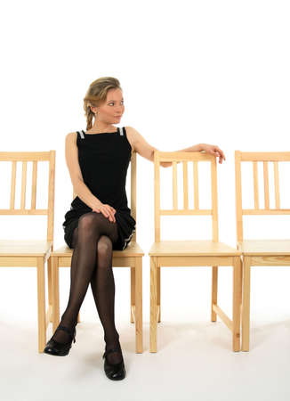 thinking woman: Young lady in black sitting on a chair and waiting for someone.
