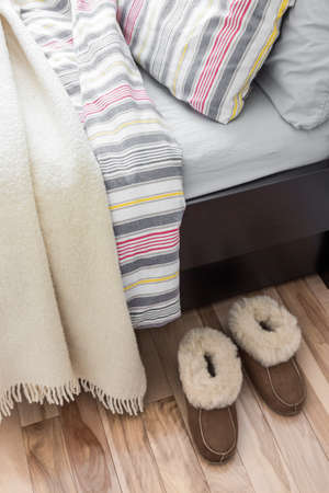 Cozy slippers on the floor, near a bed with striped bed linen  photo
