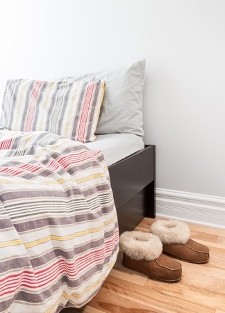 bedlinen: Warm cozy slippers near a bed with striped bed linen  Stock Photo