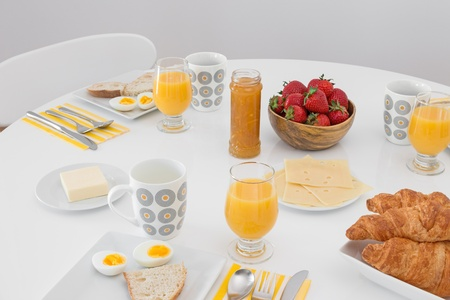 round chairs: Breakfast is ready  Simple tasty morning meal on a white table  Stock Photo