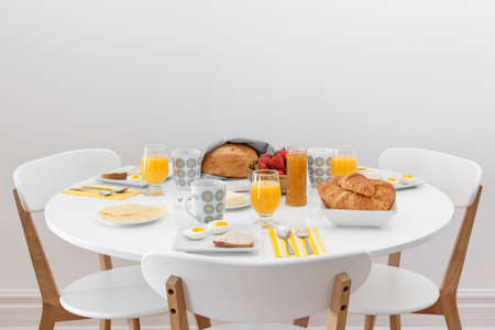 dining table and chairs: Breakfast for three  Simple tasty morning meal on a white table  Stock Photo