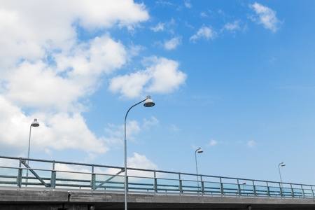lamp on the pole: Street lights on a highway, under blue sky with clouds
