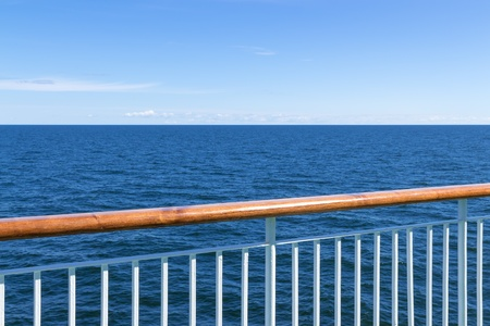 rails: Passenger ship railing with sea and blue sky in the background  Stock Photo
