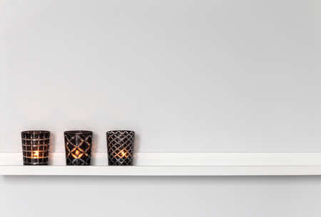 Home decor, candle lights on a white shelf  Stock Photo