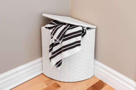 White laundry basket with striped towels in the room corner Stock Photo - 22399646