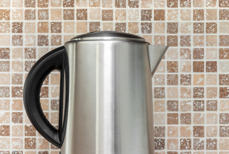electric kettle: Metal electric kettle on kitchen tile background  Stock Photo