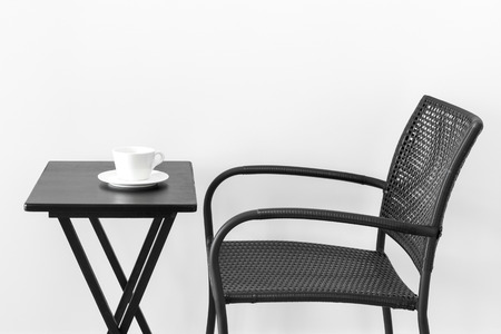Black chair, table and white cup of tea or coffee  Stock Photo - 22444912
