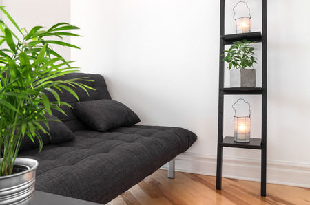 futon: Living room with gray sofa, decorated with plants and lanterns