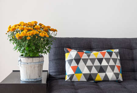 living room sofa: Bright cushion on a sofa, and orange chrysanthemums on a side table.