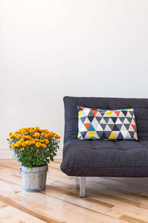 room for text: Orange chrysanthemums and gray sofa decorated with bright cushion.