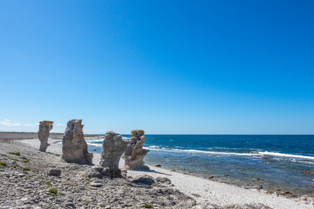 Cliff formations at the rocky coast of F�r� island in Gotland, Sweden  These cliffs are called  rauk  in Swedish  photo