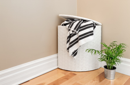 messy room: Laundry basket with striped towels and green plant in the room corner