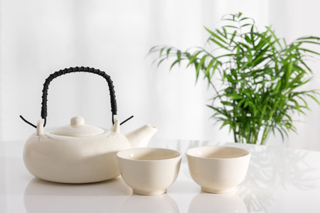 chinese tea pot: White ceramic teapot and cups on the table, with green plant in the background