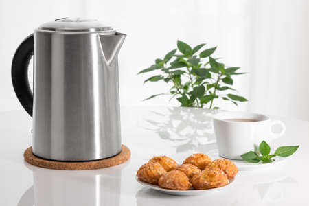 electric kettle: Teatime  Electric kettle, teacup and cookies on a table  Stock Photo