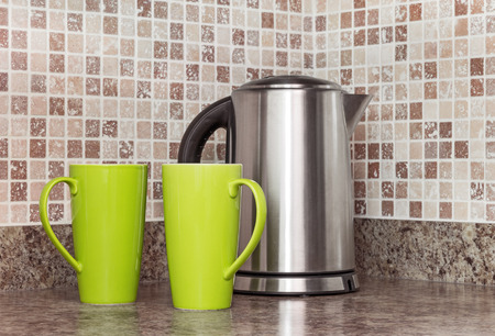 Metal electric kettle and green cups in the kitchen. photo