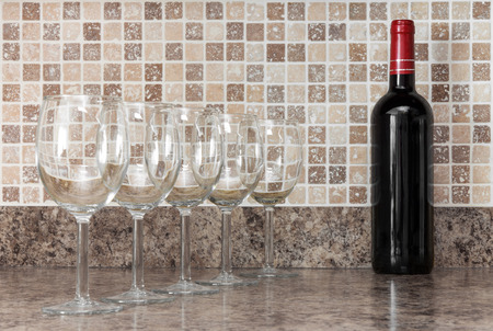 Bottle of red wine and empty glasses on kitchen countertop. photo