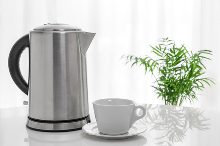 electric kettle: White cup and electric kettle on the table, with green plant in the background.