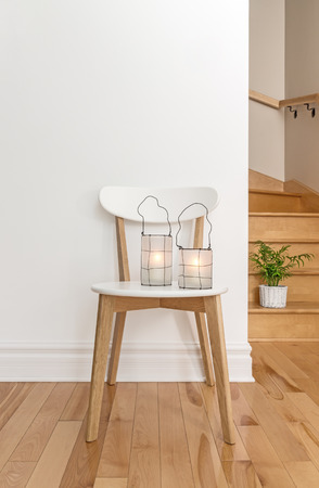 Lanterns on a white chair, in a room with staircase.