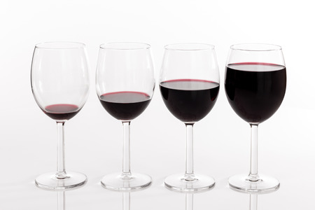 quantity: Four glasses filled with different quantities of red wine