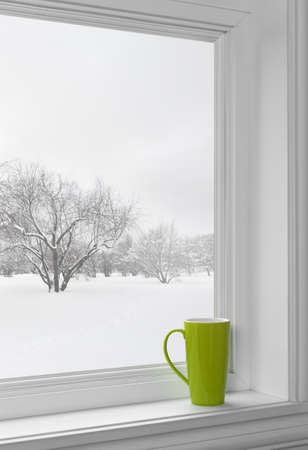 Green cup on a windowsill, with winter landscape seen through the window.