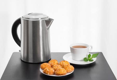 electric kettle: Teatime. Electric kettle, cup of tea and cookies on a black table. Stock Photo