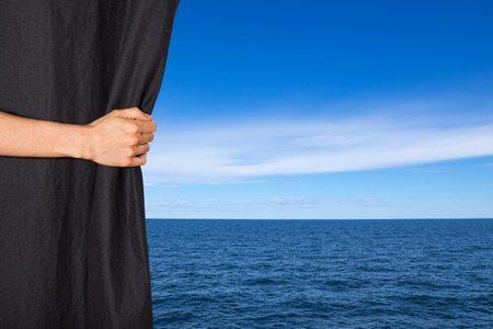 behind: Hand opening black curtain with sea and blue sky behind it. Stock Photo