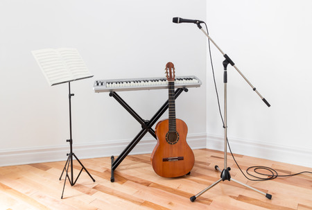 a rehearsal: Musical instruments in a room. Electric piano, guitar, microphone and stand with sheet music.