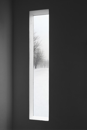 Looking at winter landscape outside the window of a dark room  photo