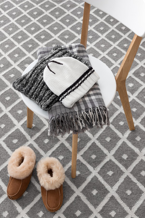 Warm slippers and winter clothes on a chair. photo