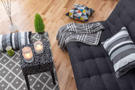 luz de velas: Detalle de un luminoso salón moderno con sofá gris. Foto de archivo